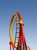 Rollercoaster loop. Red and yellow rollercoaster with clear blue sky Royalty Free Stock Photo