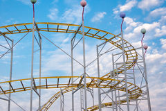 Rollercoaster rails in the evening against blue sky. Rollercoaster rails in the evening against blue sky and white clouds stock photo