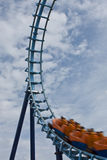 Rollercoaster Ride. A rollercoaster track against a cloudy blue sky with the carriages entering a loop Stock Photo