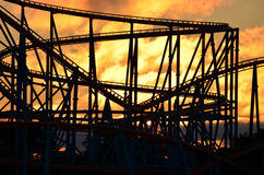 Rollercoaster Sunrise. Sunrise shinning through the clouds behind a rollercoaster royalty free stock photo