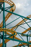 Rollercoaster Track. Yellow and green rollercoaster track, without cars, against a blue sky Royalty Free Stock Image
