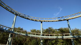 Rollercoaster train is moving along the loop stock video footage