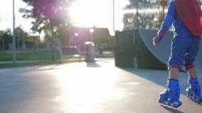Rollerdrome, niño activo en el traje y el casco del super héroe está pasando activamente tiempo en aire abierto metrajes