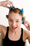 Rollers. Beautiful young woman curls her hair with curlers Royalty Free Stock Photos