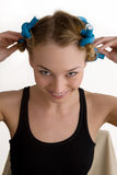 Rollers. Beautiful young woman curls her hair with curlers Stock Photos