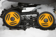 Rollers yellow and black caterpillars of the snowmobile with the Stock Photography