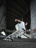 Rollerskater. Wide angle photo of a rollerskater performing extreme braking (Power Slide element) in urban scenery Stock Image