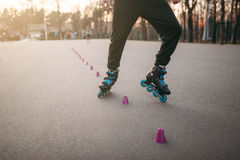 Rollerskater, rollerskating trick exercise in park. Male roller skater leisure on sidewalk Stock Image