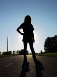 Rollerskater silhouette. Young girl addore rollerskating on the sunset road Royalty Free Stock Photo