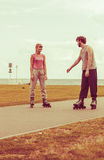 Rollerskates de port de couples regardant l'un l'autre Image stock