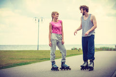 Rollerskates de port de couples regardant l'un l'autre Photo libre de droits