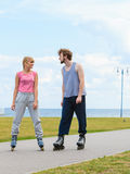 Rollerskates de port de couples regardant l'un l'autre Photo stock