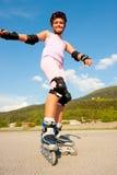 Rollerskates lindos de la chica joven en un patio Fotos de archivo