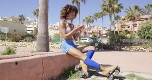 Rollerskates que llevan femeninos que se sientan en encintado almacen de metraje de vídeo