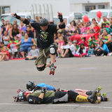 Rollerskating Daredevil. A man on roller-skates performs a stunt by jumping over two men during the K-Days (Klondike Days) summer parade in Edmonton, Alberta Royalty Free Stock Images