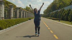 Rollerskating femenino alegre a la velocidad en la trayectoria del parque almacen de video