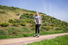 Rollerskating hermoso del adolescente en parque Fotografía de archivo libre de regalías