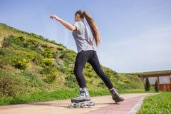 Rollerskating hermoso del adolescente en parque Imágenes de archivo libres de regalías