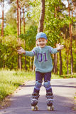 Rollerskating joven del muchacho en el parque Foto de archivo