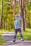 Rollerskating joven del muchacho en el parque Fotografía de archivo libre de regalías