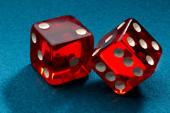 Rollin' Red Dice. A pair of red transparent dice shot on blue felt royalty free stock photography