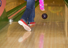 Rolling a bowling ball. Legs and arm of a girl rolling a bowling ball Stock Photography