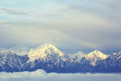 Rolling clouds and frozen mountain summits landscape Stock Photo