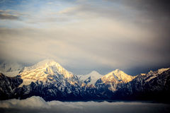 Rolling clouds and sunrise snow mountain landscape Royalty Free Stock Images