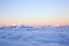 Rolling clouds and sunrise snow mountain landscape Royalty Free Stock Image