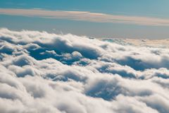 Rolling Clouds. A wave of fluffy clouds roll by an airplane window Royalty Free Stock Image