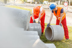 Rolling concrete pipes Stock Images