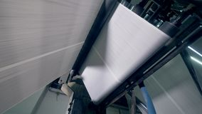 Rolling newspaper sheets on a special conveyor, bottom view. Rolling conveyor works at a print office