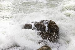 Rolling crashing waves on pebbles on a beach at Clarence Drive, between Kleinmond and Gordons Bay, Western Cape, South Africa. stock photography