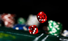 Rolling Dice. Red Craps Dice rolling on felt with poker chips royalty free stock image