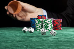 Rolling the dice. A businessman rolling the dice in a gambling game Royalty Free Stock Image