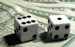 Rolling The Dice. Two dice on top of some US money Royalty Free Stock Images