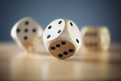 Rolling the dice. Rolling three dice on a wooden desk Stock Photos