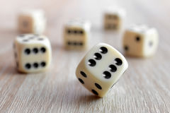 Rolling dice. On a wooden desk Stock Photo