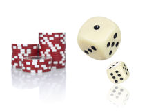Rolling dices. Pair of dice rolling in front of stacked red poker chips stock photo