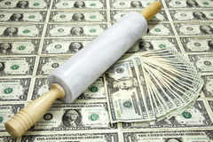 Rolling in the Dough. Rolling pin on a sheet of money representing the saying Rolling in Dough Royalty Free Stock Photos