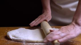 Rolling the dough with a rolling pin on the table. Close-up 4K.  stock video