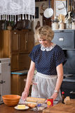 Rolling the Dough. A senior woman making a pie in clothing and kitchen in the 1940's stock photo