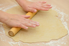 Rolling the dough on a wooden table. Using a rolling pin Royalty Free Stock Image