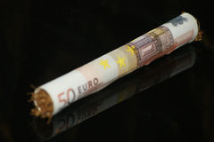 Rolling 50 euro part II. Rolling money papers and tobacco royalty free stock images