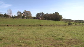 Rolling farm land with farmhouse in the background stock footage