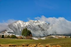 Rolling fields with snow covered mountains royalty free stock images