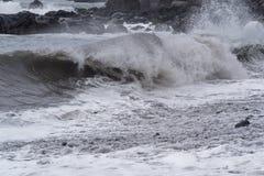 Rolling golven op steenkustlijn bij stormachtig weer royalty-vrije stock fotografie