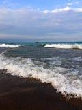 Rolling golven op strand met lang zeilschip in afstand Stock Fotografie