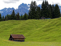 Rolling hills with hut in Bavarian Alps at spring. Unique rolling hills landscape of the alpine upland with a mountain range in the background. A characteristic Stock Images