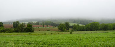 Rolling hills, fields and meadows under foggy low cloud cover,  Greenwood, Nova Scotia. Royalty Free Stock Photo